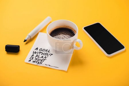 Photo for Coffee cup on paper napkin with goal without plan just wish inscription, smartphone and felt-tip pen on yellow desk - Royalty Free Image