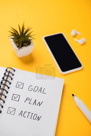 Photo pour Notebook with goal, plan, action words near smartphone, potted plant, wireless earphones and felt-tip pen on yellow desk - image libre de droit