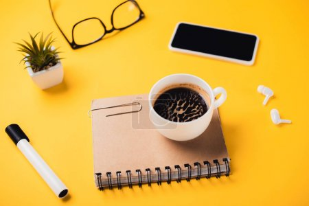 Photo pour Tasse de café sur un ordinateur portable près d'un téléphone intelligent, écouteurs sans fil, verres, plantes en pot et feutre sur un bureau jaune - image libre de droit