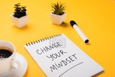 Photo for Notebook with change your mindset inscription near coffee cup, potted plants and felt-tip pen on yellow desk - Royalty Free Image