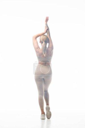 back view of blonde girl in beige leggings twerking in smoke isolated on white