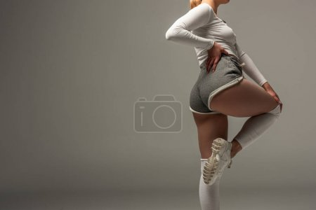 Photo for Partial view of young sexy girl in shorts twerking on grey background - Royalty Free Image