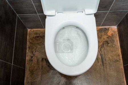 Photo pour Cuvette de toilette propre en céramique avec chasse d'eau dans la toilette moderne avec carrelage gris - image libre de droit