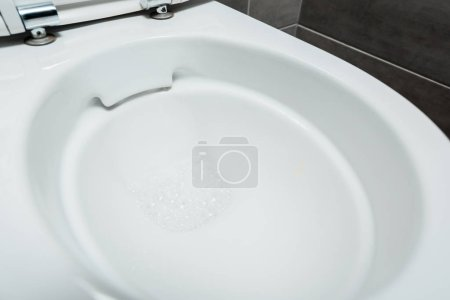 Photo for Close up view of ceramic clean toilet bowl with foam in modern restroom - Royalty Free Image