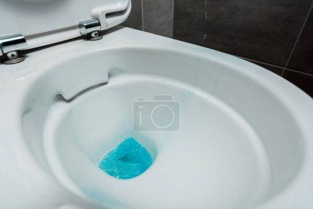 Photo pour Vue de près du détergent liquide bleu dans une cuvette en céramique propre dans une toilette moderne avec carrelage gris - image libre de droit