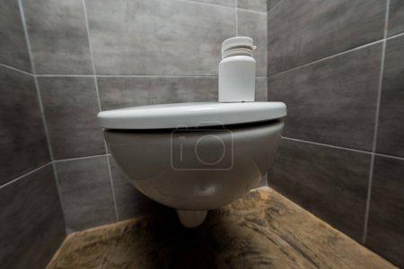 Foto de Container with pills on ceramic clean toilet bowl in modern restroom with grey tile - Imagen libre de derechos