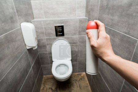 Foto de Cropped view of man holding air freshener in modern restroom with grey tile - Imagen libre de derechos