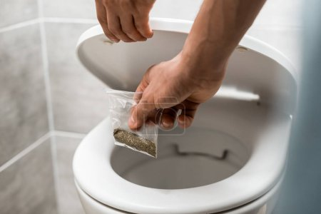 Photo for Cropped view of man throwing away marijuana in toilet bowl - Royalty Free Image