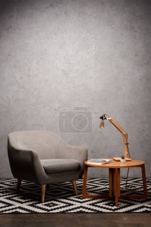 Photo pour Interior of living room with comfortable grey modern armchair near wooden table and lamp on carpet - image libre de droit