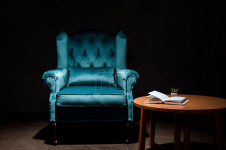Photo pour Elegant velour blue armchair near wooden table with book isolated on black - image libre de droit