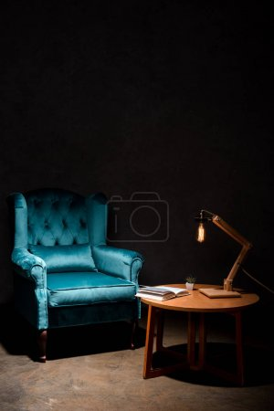 Photo pour Elegant velour blue armchair with pillow near wooden table and lamp isolated on black - image libre de droit