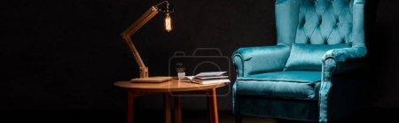 Photo pour Élégant fauteuil en velours bleu avec oreiller près d'une table en bois et d'une lampe isolée sur fond noir, photo panoramique - image libre de droit