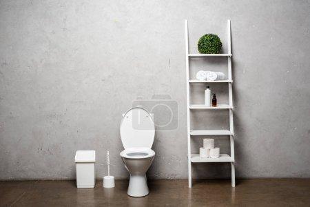 Photo pour Intérieur d'une salle de bain moderne avec cuvette de toilette près d'un support avec produits cosmétiques, serviettes, papier hygiénique, poubelle et brosse de toilette - image libre de droit