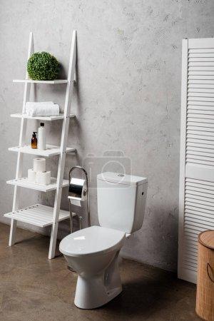 Photo pour Intérieur d'une salle de bain moderne avec cuvette de toilette près d'une étagère avec produits de beauté, serviettes, papier hygiénique, panier à linge et brosse de toilette - image libre de droit