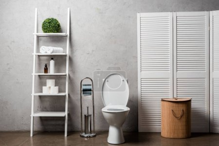 interior of modern bathroom with toilet bowl near rack with cosmetics, towels, toilet paper, laundry basket and toilet brush
