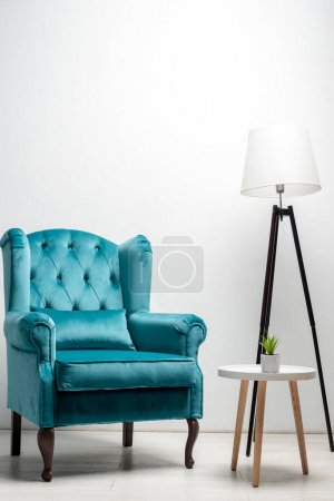 Photo for Elegant velour blue armchair with pillow near coffee table and floor lamp - Royalty Free Image