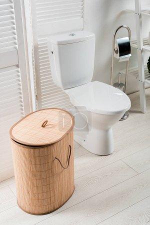 Photo pour Intérieur d'une salle de bain moderne et blanche avec cuvette près d'un écran rabattable, panier de lessive, brosse de toilette - image libre de droit