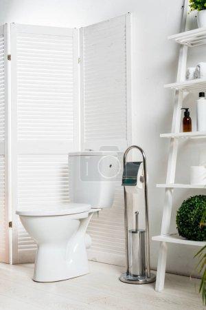 Photo pour Intérieur d'une salle de bain moderne et blanche avec cuvette près d'une grille pliante, d'un support et de plantes - image libre de droit