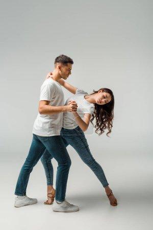 Photo pour Danseurs en t-shirts et jeans dansant bachata sur fond gris - image libre de droit