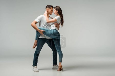 Photo for Dancers in t-shirts and jeans dancing bachata on grey background - Royalty Free Image