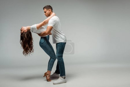 Photo for Side view of dancers in t-shirts and jeans dancing bachata on grey background - Royalty Free Image