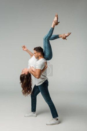 Photo pour Vue latérale des danseurs en t-shirts et jeans dansant bachata sur fond gris - image libre de droit