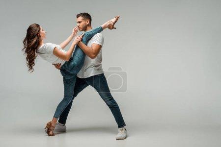 Foto de Bailarines con camisetas y vaqueros bailando bachata en fondo gris. - Imagen libre de derechos