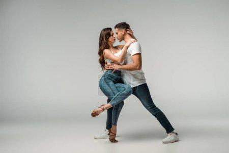 Photo pour Danseurs en jeans denim dansant bachata sur fond gris - image libre de droit
