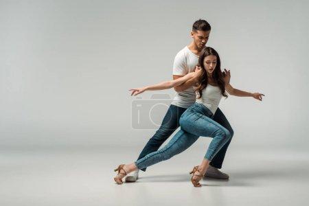 Photo pour Danseurs en jeans en denim dansant bachata sur fond gris - image libre de droit