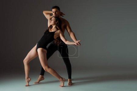 Photo pour Danseurs sexy aux yeux fermés dansant contemporain sur fond sombre - image libre de droit