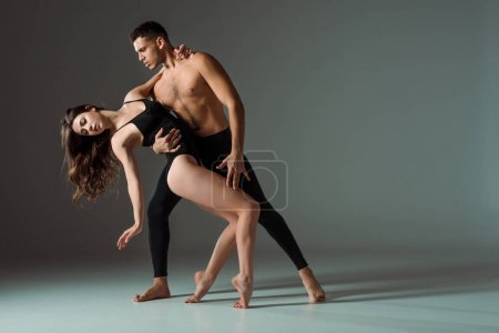 Photo for Sexy dancers dancing contemporary on dark background with copy space - Royalty Free Image
