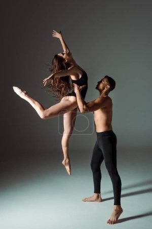 Foto de Bailarines guapos y atractivos bailando contemporáneo sobre fondo oscuro. - Imagen libre de derechos