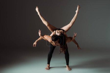 Photo pour Sexy danseurs dansant la danse contemporaine sur fond sombre - image libre de droit