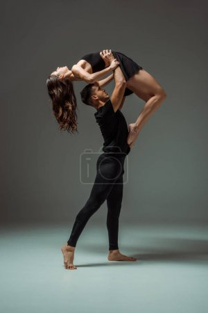 Photo for Side view of handsome and attractive dancers dancing contemporary on dark background - Royalty Free Image