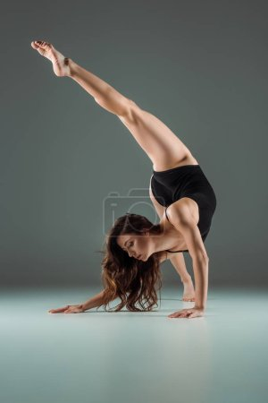 Photo for Attractive dancer in black bodysuit dancing contemporary on dark background - Royalty Free Image