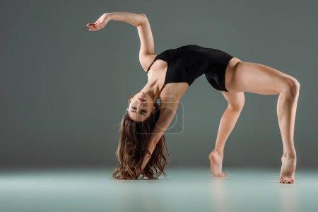 Photo pour Jolie danseuse en costume corporel noir danse contemporaine sur fond sombre - image libre de droit