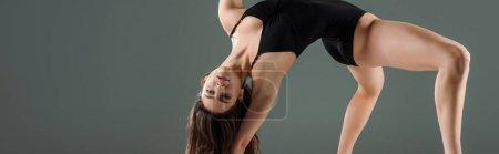 Foto de Foto panorámica de bailarín atractivo en traje de cuerpo negro bailando contemporáneo aislado en gris. - Imagen libre de derechos