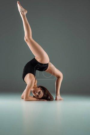 Foto de Bailarín atractivo en traje de cuerpo negro bailando contemporáneo sobre fondo oscuro. - Imagen libre de derechos