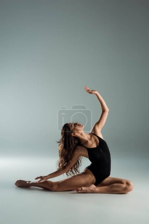 Photo for Attractive dancer in black bodysuit dancing contemporary on grey background - Royalty Free Image