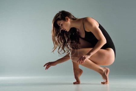 Foto de Bailarín atractivo en traje de cuerpo negro bailando contemporáneo sobre fondo gris. - Imagen libre de derechos