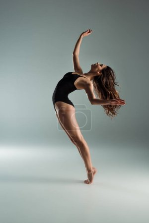 Photo for Side view of attractive dancer in black bodysuit dancing contemporary on grey background - Royalty Free Image