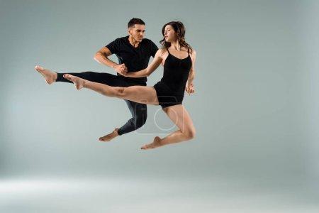Foto de Bailarines guapos y atractivos bailando contemporáneo sobre fondo gris. - Imagen libre de derechos