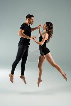 Photo pour Danseurs beaux et attrayants dansant contemporain sur fond gris - image libre de droit