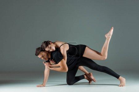 Photo pour Danseurs beaux et attrayants dansant contemporain sur fond sombre - image libre de droit
