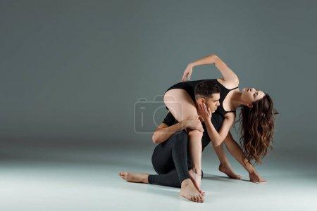danseurs beaux et attrayants dansant contemporain sur fond sombre