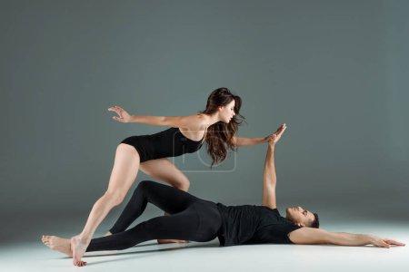Photo pour Side view of dancers dancing contemporary on dark background - image libre de droit