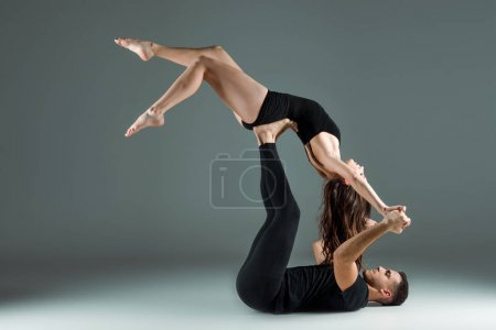 Photo for Side view of dancers dancing contemporary on dark background - Royalty Free Image
