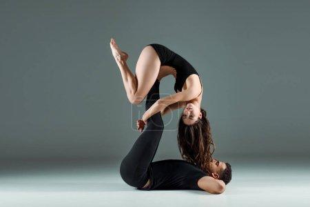 Photo pour De beaux et attrayants danseurs dansant contemporain sur fond sombre - image libre de droit