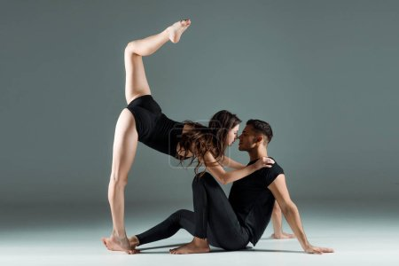 Photo pour Vue latérale de beaux et attrayants danseurs dansant contemporain sur fond sombre - image libre de droit