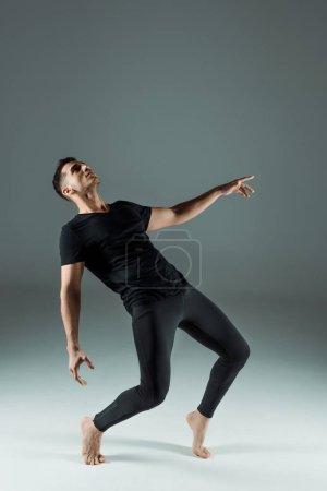 Foto de Bailarín guapo en leyendas negras y danza de camiseta contemporánea sobre fondo oscuro. - Imagen libre de derechos